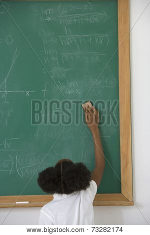 African American girl erasing blackboard