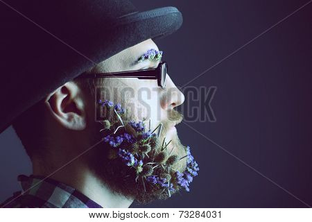 Handsome man with a beard of flowers wearing elegant bowler hat and glasses. Profile portrait.