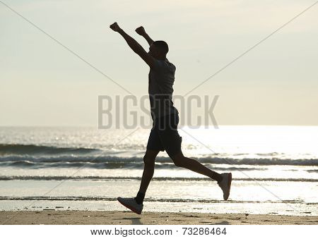 Man Running On Beach With Arms Raised