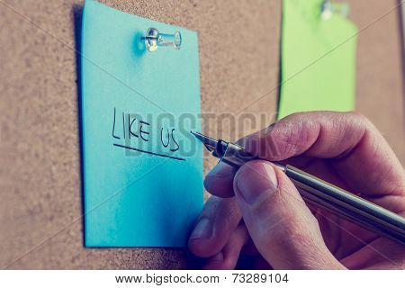 Man Writing - Like Us - On A Notice Board