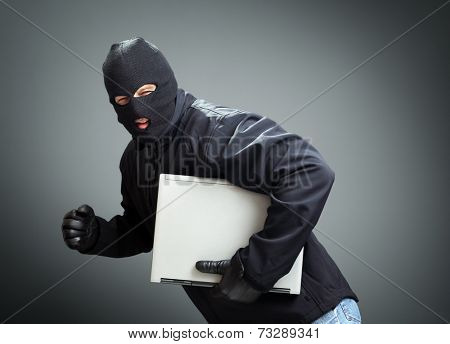 Thief stealing laptop computer concept for hacker, hacking, security or insurance
