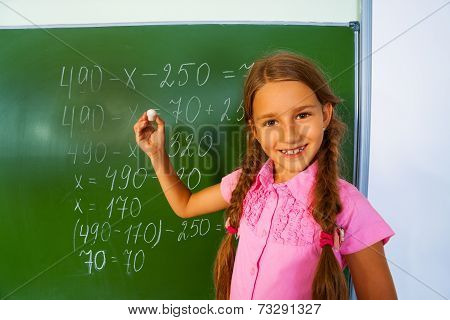 Smiling girl with braids and chalk near blackboard
