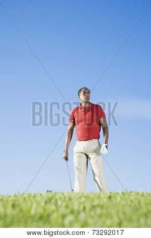 African man holding golf club