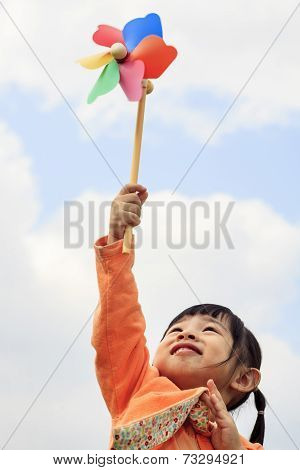 Cute Little Girl On Grass In Summer Day Holds Windmill