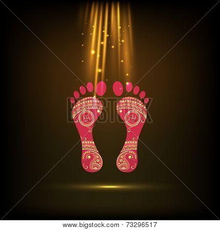 Hindu mythological Goddess Laxmi's footprint with golden rays for Diwali celebration on shiny brown background.