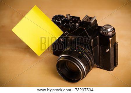 Old photo camera with empty sticky note