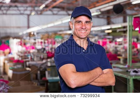 portrait of happy senior clothing factory owner