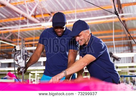 experienced textile factory co-workers cutting fabric