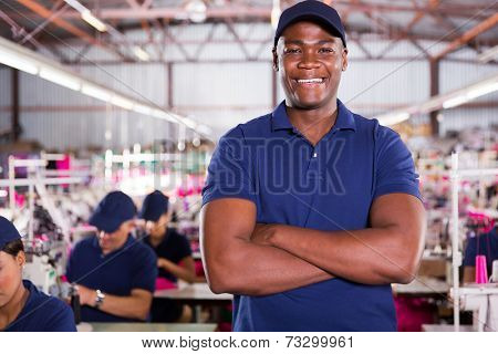 handsome african american factory supervisor with machinists on background