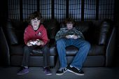 picture of video game  - Two boys sitting on a couch playing video games - JPG