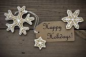 stock photo of ginger bread  - Happy Holidays Tag with some Ginger Bread Cookies with white Decoration on Wood - JPG