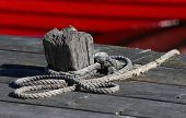 foto of bollard  - A bollard a rope and a red fishing boat in the harbour Grisslehamn Sweden - JPG