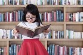 stock photo of little school girl  - Asian little girl reads book seriously in library with bookcase background - JPG