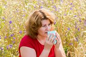 picture of rhinitis  - Fat woman with allergic rhinitis in the meadow - JPG