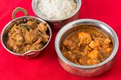stock photo of kadai  - Chili garlick chicken and malabar chicken curry with cashew rice on a red tablecloth - JPG