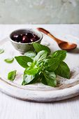 stock photo of kalamata olives  - Fresh Basil and Kalamata Olives on a Chopping Board - JPG