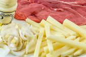 stock photo of chicory  - Raw Drierib steak and fries with chicory and mayonnaise - JPG