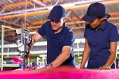 picture of cut  - senior textile worker teaching new employee about cutting material - JPG