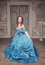 stock photo of pompous  - Young beautiful medieval woman in long blue dress in the old room - JPG