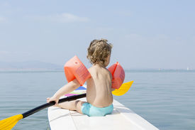 picture of manga  - rear view of a child sitting on a paddle board holding a paddle over a calm sea MInor Sea La manga Murcia Spain - JPG