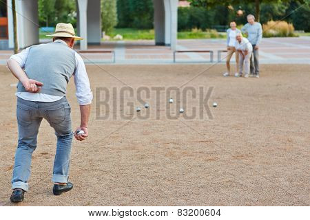 Senior group playing boule together in a city in front of a retirement hime