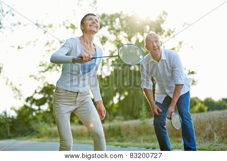 Senior couple playing badminton in summer in nature