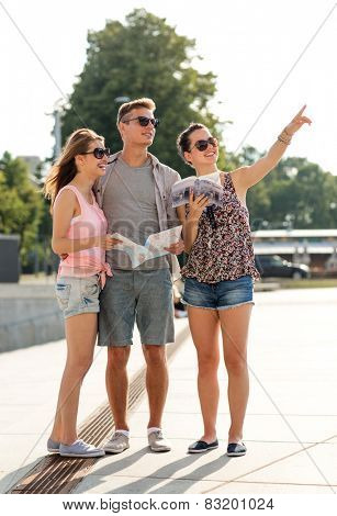 friendship, travel, tourism, vacation, summer and people concept - smiling friends with map and city guide pointing finger outdoors