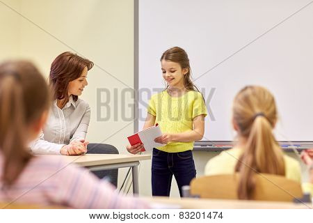 education, elementary school, learning and people concept - group of school kids with teacher in classroom