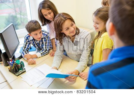 education, elementary school, learning and people concept - group of school kids with teacher talking in classroom