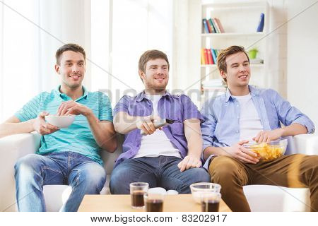 friendship, sports and entertainment concept - happy male friends with snacks watching tv at home