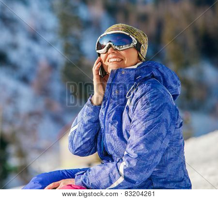 Woman Talks via the Phone On Mountain Ski Resort