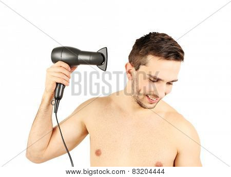 Handsome young man blow drying his hair isolated on white