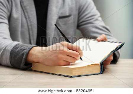 Author signing autograph in own book at wooden table on light blurred background