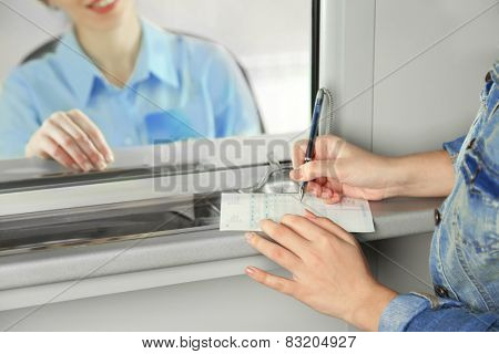 Teller window with working cashier and female hands with claim check. Concept of payment of utilities