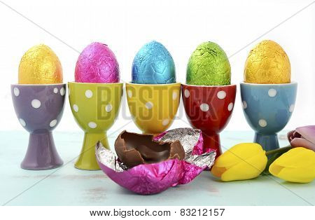 Happy Easter Row Of Chocolate Eggs Wrapped In Bright Color Foil In Red, Yellow, Blue, Green And Purp