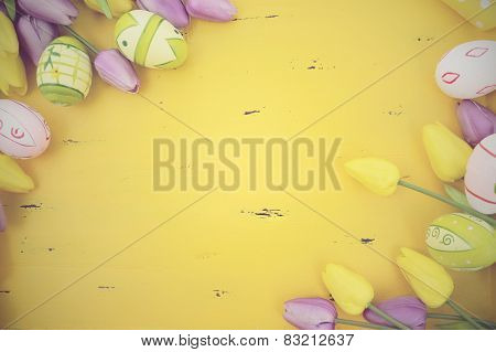 Happy Easter Background With Painted Easter Eggs, Yellow And Purple Silk Tulips And Polka Dot Ribbon