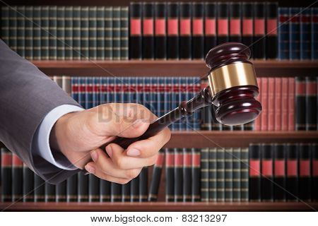 Male Judge Hand Striking The Gavel