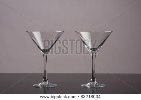 Two Martini glasses standing on dark table
