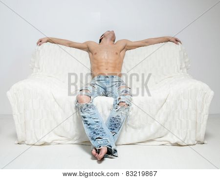 muscular man in torn jeans sitting on the sofa