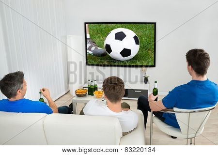 Three Men Watching Soccer Match
