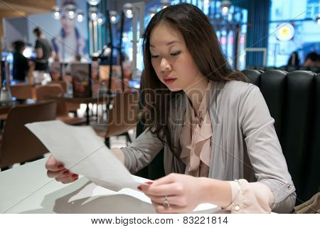 Beautiful Asian girl reading a letter