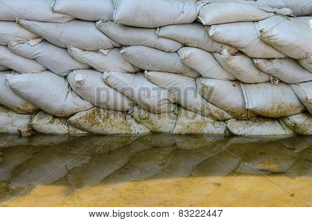 White Sandbags For Flood Defense And It's Reflection Brown Water