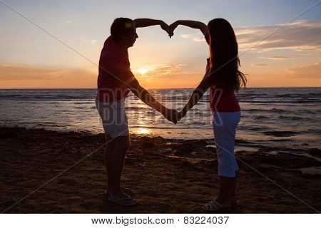 Couple Making Heart Shape At Beach