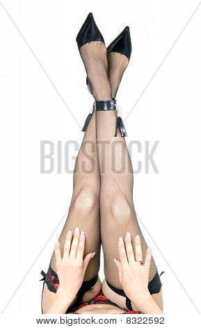 Female feet in shoes and openwork stockings