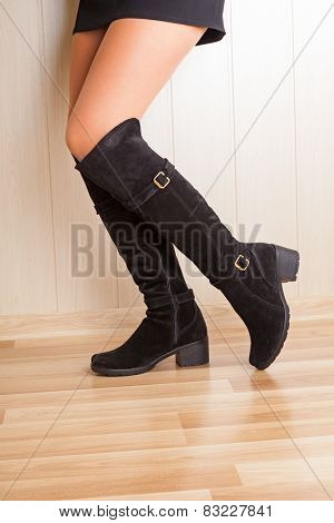 A boots with beautiful legs on wood