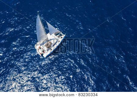 Amazing view to Catamaran cruising in open sea at windy day. Drone view - birds eye angle