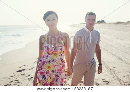 Couple Walking On Camera. Focus On Woman. Young Happy Couple Walking On Beach Smiling, Holding Aroun
