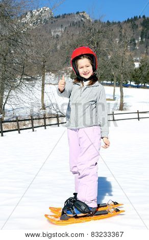 Little Girl With Snowshoes And The Helmet In The Winter
