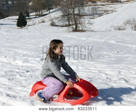 Young Girl Plays With The Red Sled On The Snow