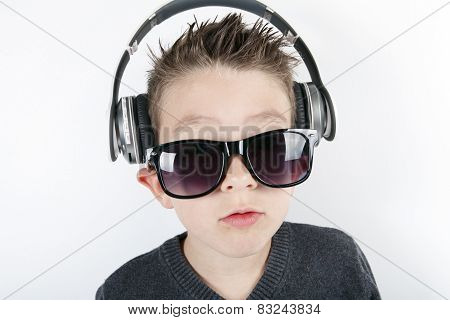 Young boy wearing headphones listening music in studio.